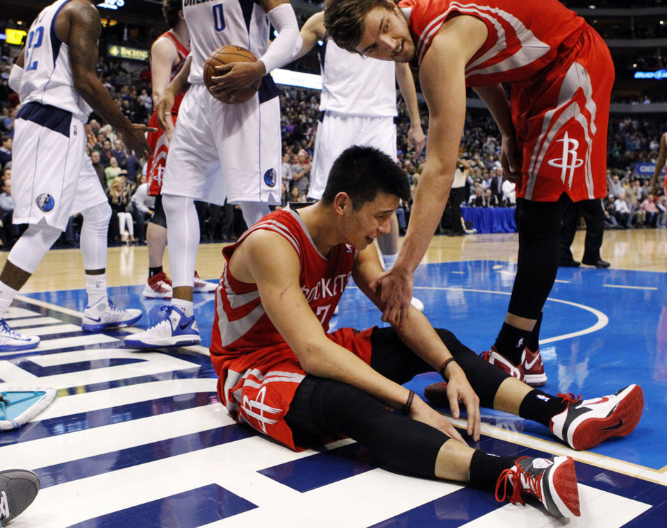 Photo - Houston Rockets guard Jeremy Lin (7) is helped by Chandler Parsons (25) after being knocked to the court and called for a foul during the fourth quarter of an NBA basketball game against the Dallas Mavericks, Wednesday, Jan. 16, 2013, in Dallas. The Mavericks won 105-100. (AP Photo/John F. Rhodes)