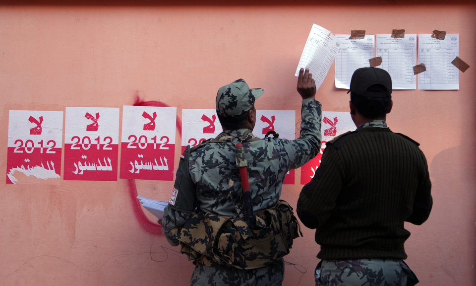 Photo - Egyptian military officers hang the list of voters names next to stickers with Arabic writing that reads