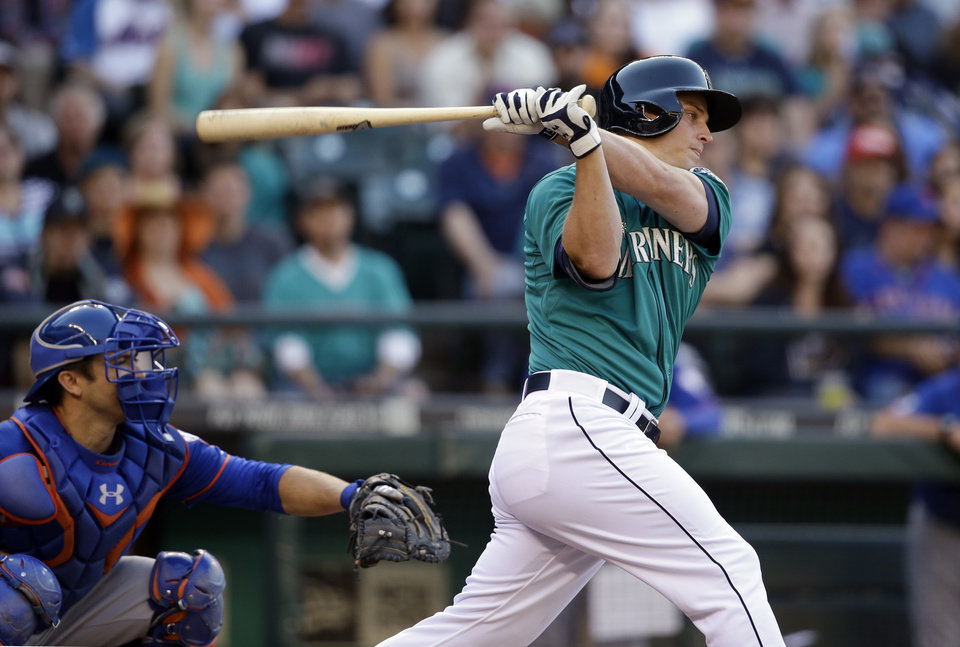 Photo - Seattle Mariners' Kyle Seager singles in a run as New York Mets catcher Travis d'Arnaud looks on in the first inning of a baseball game Monday, July 21, 2014, in Seattle. (AP Photo/Elaine Thompson)