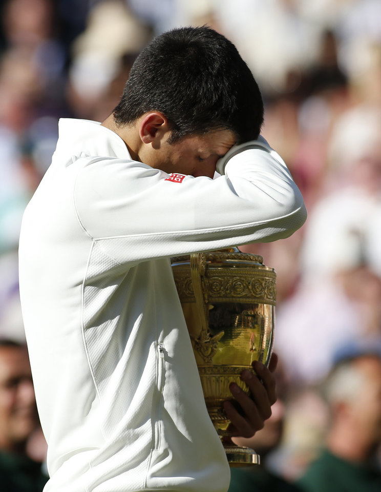 Photo - Novak Djokovic of Serbia wipes his eye as he holds the trophy after defeating Roger Federer of Switzerland in the men's singles final at the All England Lawn Tennis Championships in Wimbledon, London, Sunday, July 6, 2014. (AP Photo/Sang Tan, Pool)