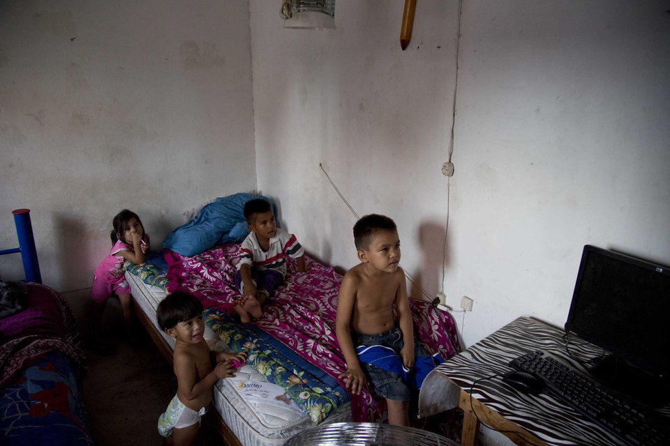 Photo - In this July 10, 2014, photo, children watch television at the