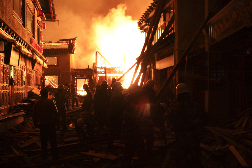 Photo - Firefighters fortify a wooden building while a fire ravages ancient Dukezong town in Shangri-la county, in southwestern China's Yunnan province, Saturday Jan. 11, 2014. The 10-hour inferno has razed the ancient Tibetan town in the province that's popular with tourists. (AP Photo) CHINA OUT