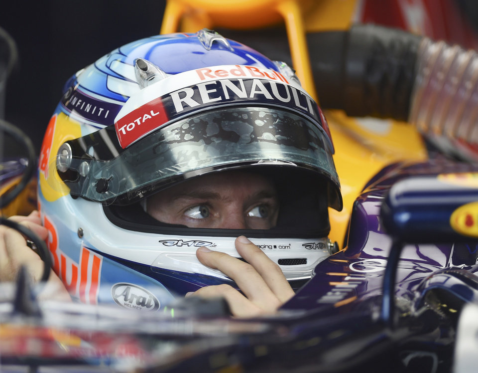 Photo - Red Bull driver Sebastian Vettel of Germany sits in his car during the third practice session at Albert Park ahead of the Australian Formula One Grand Prix in Melbourne, Australia, Saturday, March 15, 2014. (AP Photo/Ross Land)