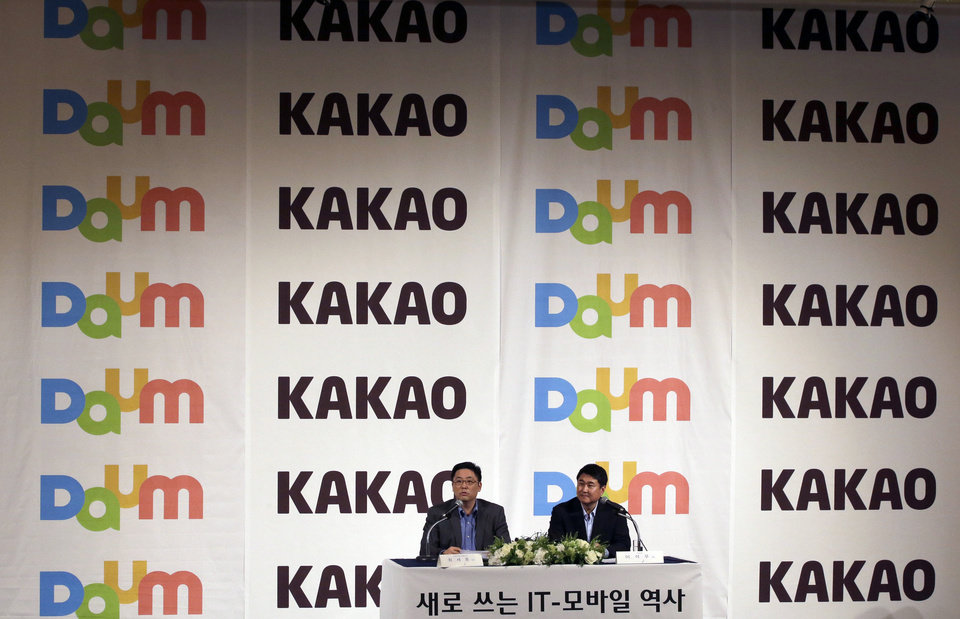 Photo - Daum Communications Corp. CEO Choi Sae-hoon, left, answers reporter's question as Kakao Corp. CEO Sirgoo Lee listens during their press conference in Seoul, South Korea, Monday, May 26, 2014. Mobile messenger service Kakao Talk is seeking a backdoor listing on the South Korean stock exchange by combining with the country's second largest Internet portal. (AP Photo/Lee Jin-man)