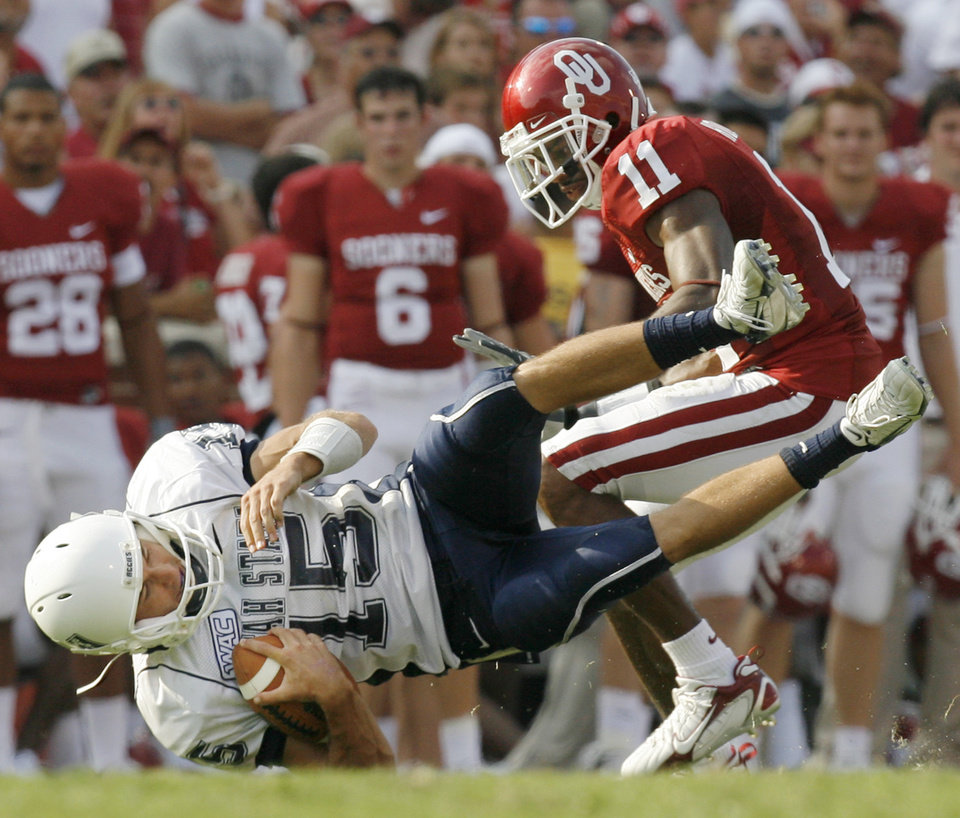 Photo - Utah State's Jase McCormick (15) loses yard after a bad snap as Lendy Holmes (11) defends in the second half during the University of Oklahoma Sooners (OU) college football game against the Utah State University Aggies (USU) at the Gaylord Family -- Oklahoma Memorial Stadium in Norman, Okla., on Saturday, Sept. 15, 2007. OU won, 54-3. By NATE BILLINGS, The Oklahoman  ORG XMIT: KOD