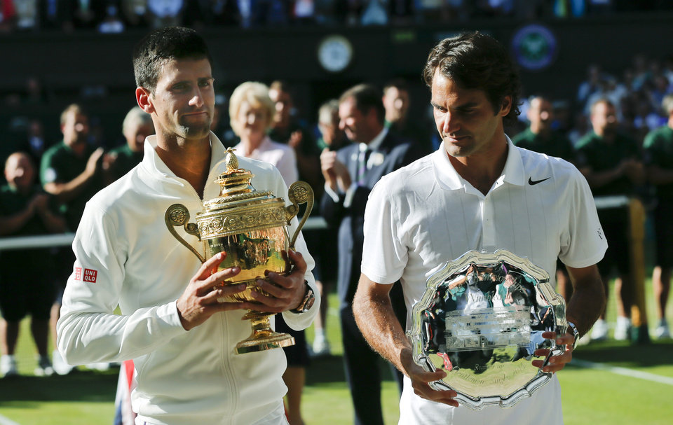 Photo - Serbia's Novak Djokovic, left, holds his trophy after defeating Switzerland's Roger Federer, right, in the men's singles final match at the All England Lawn Tennis Championships in Wimbledon, London, Sunday, July 6, 2014. (AP Photo/Ben Curtis)
