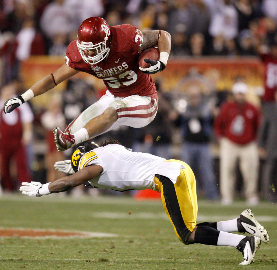 Oklahoma's Trey Millard (33) leaps over Iowa's Jordan Bernstine (4) during the Insight Bowl college football game between the University of Oklahoma (OU) Sooners and the Iowa Hawkeyes at Sun Devil Stadium in Tempe, Ariz., Friday, Dec. 30, 2011. Photo by Bryan Terry, The Oklahoman