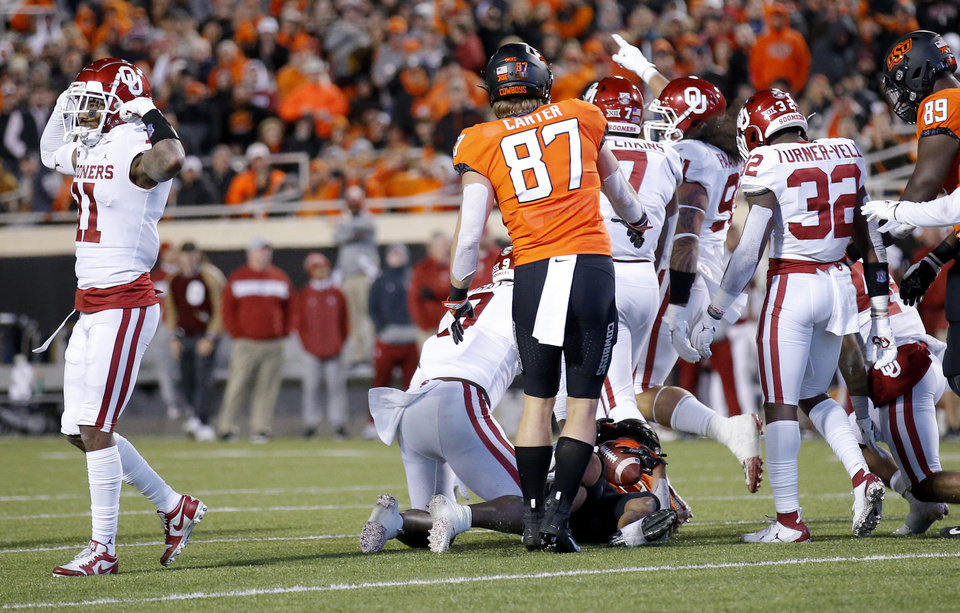 Photo - Oklahoma's Parnell Motley (11) celebrates a stop on Oklahoma State's Chuba Hubbard (30) in the second quarter during the Bedlam college football game between the Oklahoma State Cowboys (OSU) and Oklahoma Sooners (OU) at Boone Pickens Stadium in Stillwater, Okla., Saturday, Nov. 30, 2019. [Sarah Phipps/The Oklahoman]