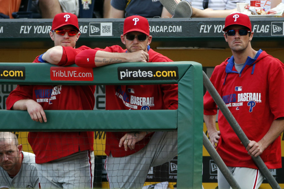 Photo - ADVANCE FOR USE SUNDAY, JULY 20 - FILE - In this July 5, 2014, file photo, Philadelphia Phillies starting pitchers A.J. Burnett, center, Kyle Kendrick, left, and Cole Hamels, right, stand in the dugout during the ninth inning of a baseball game against the Pittsburgh Pirates in Pittsburgh.  The Phillies are less than three years removed from a dominant run of five straight NL East titles, two pennants and one World Series championship. Despite having the highest payroll in franchise history, they are headed toward another last-place finish. (AP Photo/Gene J. Puskar, File)