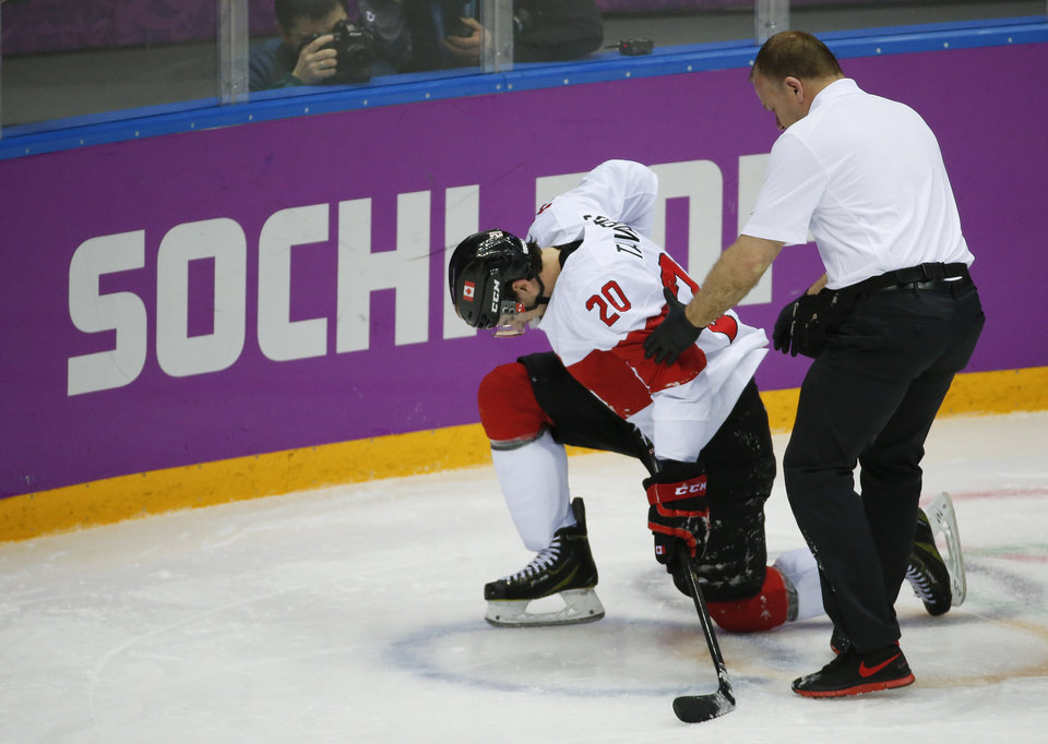 Photo - Canada forward John Tavares is helped up off the ice by a trainer during the second period of a men's quarterfinal ice hockey game against Latvia at the 2014 Winter Olympics, Wednesday, Feb. 19, 2014, in Sochi, Russia. Tavares is out for the rest of the Olympics with an unspecified leg injury. (AP Photo/Mark Humphrey)