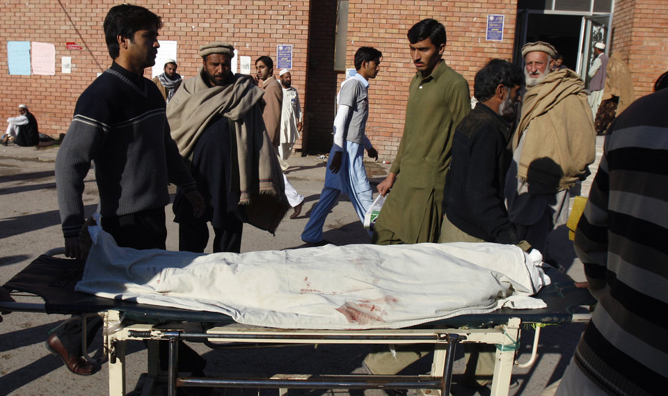 Photo - Pakistani relatives transport the dead body of a female polio worker who was killed by gunmen at a local hospital in Peshawar, Pakistan, Tuesday, Dec. 18, 2012. Gunmen killed several people working on a government polio vaccination campaign in two different Pakistani cities on Tuesday, officials said. The attacks were likely an attempt by the Taliban to counter an initiative the militant group has long opposed. (AP Photo/Mohammad Sajjad)