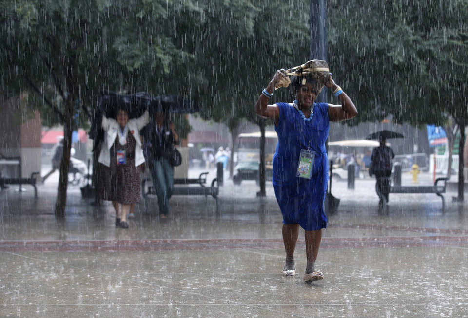 Photo -   Delegates run for shelter in a downpour as they arrive at the Democratic National Convention in Charlotte, N.C., on Thursday, Sept. 6, 2012. (AP Photo/Jae C. Hong)