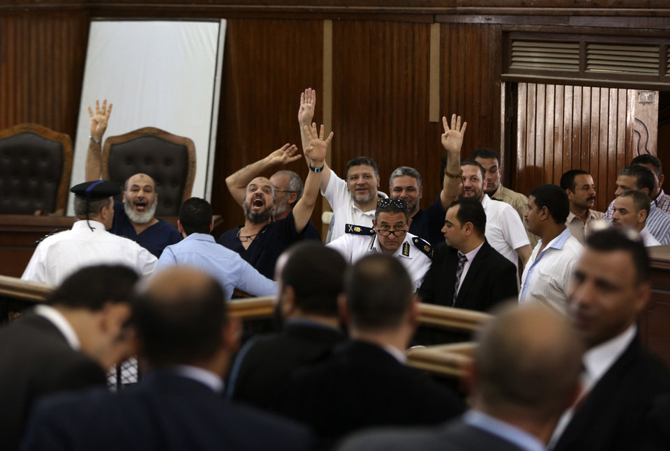 Photo - Members of the banned Muslim Brotherhood enter a courtroom brandishing the four-fingered sign symbolizing the sit-in at Cairo's Rabaah al-Adawiya mosque, where hundreds were killed last August, in Cairo, Egypt, Saturday, July 5, 2014. Egyptian judicial officials say a Cairo court has upheld death sentences against 10 members of the Brotherhood and sentenced 38 others to life, including the spiritual leader of the Islamist group. Saturday's verdicts are part of an ongoing crackdown against Islamists that began after the military's ouster last year of President Mohammed Morsi, who hails from the Brotherhood. (AP Photo/Mostafa Elshemy)