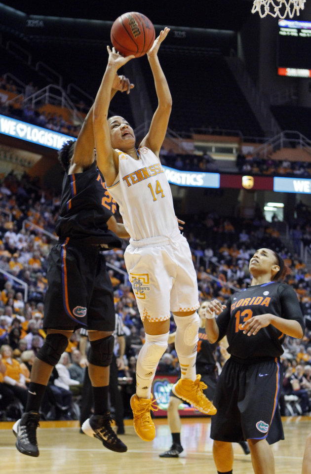Photo - Tennessee guard Andraya Carter (14) is fouled from behind by Florida guard Kayla Lewis (22) in the first half of an NCAA college basketball game Thursday, Jan. 23, 2014, in Knoxville, Tenn. (AP Photo/Wade Payne)
