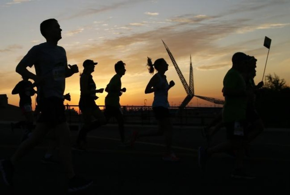 Photo -  Runners are silhouetted with the Skydance Bridge in the background as they run south across the bridge over Interstate 40 at Walker Ave. on Sunday at the Oklahoma City Memorial Marathon. [Nate Billings/The Oklahoman]