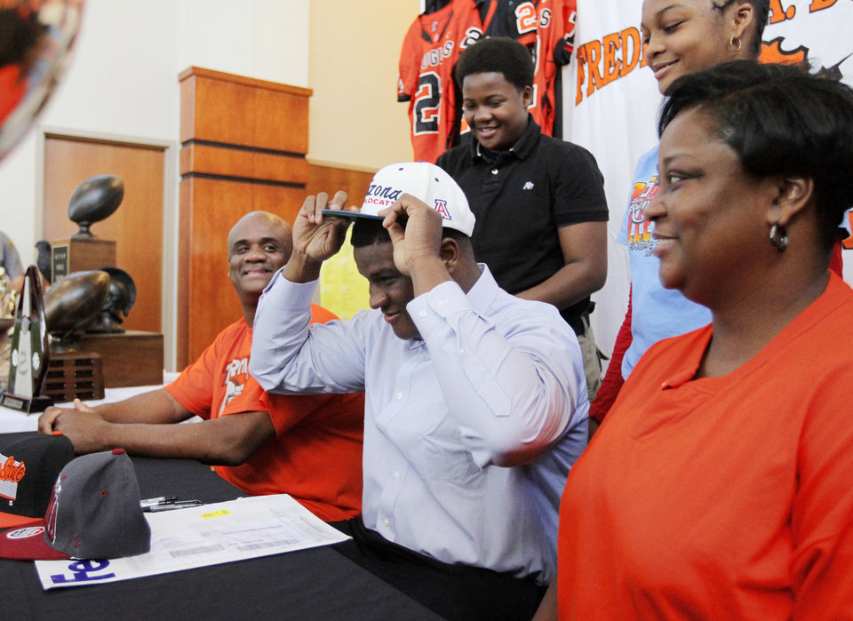 Photo - Cayman Bundage puts on a University of Arizona cap confirming his commitment to play football for the Wildcats as he is surrounded by his family, including father Clyde Bundage, left, mother LaDonna Bundage, right, brother Calvin Bundage, upper left, and sister Alise Bundage, upper right, during the National Signing Day ceremony at Douglass High School in Oklahoma City, Wednesday, Feb. 1, 2012. Photo by Nate Billings, The Oklahoman