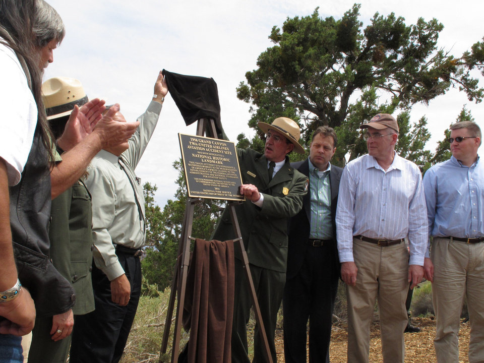 Photo - Grand Canyon National Park Superintendent Dave Uberuaga, center, unveils a plaque at the northern Arizona park on Tuesday, July 8, 2014 that marks the site of a 1956 commercial airliner collision over the canyon as a National Historic Landmark. (AP Photo/Felicia Fonseca)