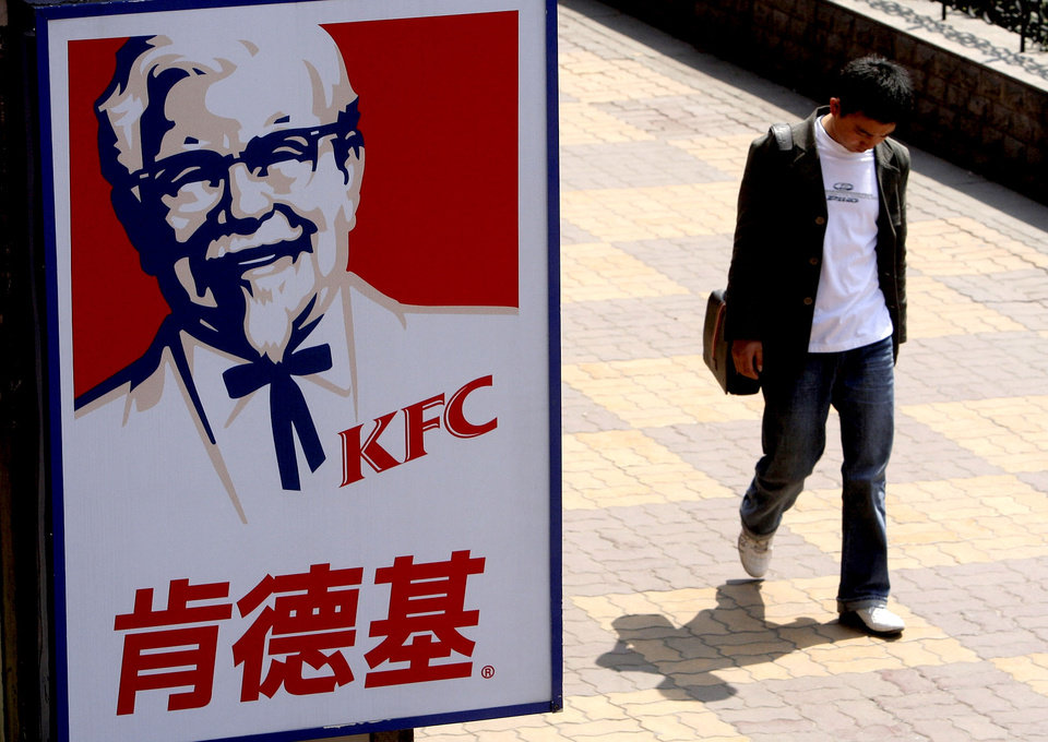 FILE - In this Thursday, March 29, 2007, file photo, a man walks past a sign for KFC in Shanghai, China. The owner of KFC and Pizza Hut said Thursday, Dec. 6, 2012, it is taking its fast-food menus to the lesser-known regions of China, with plans to set up shop in smaller cities throughout the key market. After expanding in China\'s biggest cities in recent years, Yum Brands Inc. is focusing on populating the country\'s less urbanized areas. (AP Photo/Eugene Hoshiko)