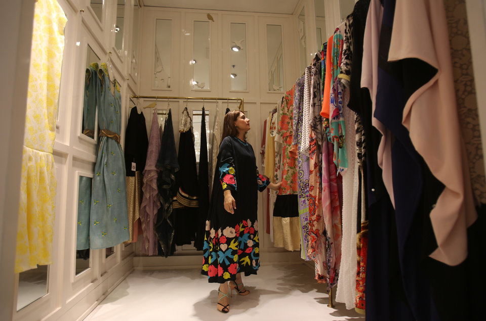 In this Tuesday, July 14, 2014 photo, Shayma, the manager of the Sauce boutique, presents the Ramadan collection at their Jumeirah branch in Dubai, United Arab Emirates. From Cairo to Dubai, local designers create everything from special Ramadan-themed purses and kaftans to towels, candles and tablecloths. For some, the stylish accessories help create a festive atmosphere unique to Ramadan, but for others it is a sign of the growing commercialization of Islam's holiest month. (AP Photo/Kamran Jebreili)
