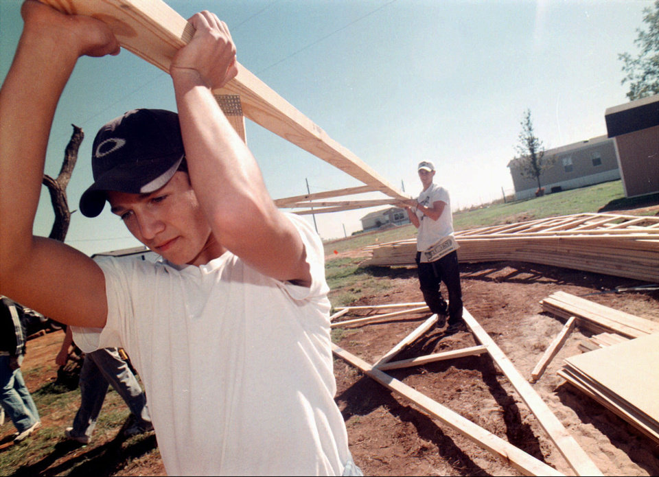 Photo - Eric Perales, a volunteer from Grace United Methodist Church in Mustang, carries a section of a roof toward a home under construction in Mulhall, on Oct. 20, 1999, in this archive photo. Central Oklahoma Habitat for Humanity volunteers helped rebuild the home of Lisa Schmidt after it was destroyed in a May 3 tornado. Habitat is readying for rebuilding again after the round of tornadoes last Sunday and Monday.  JOHN CLANTON  ENID - AP PHOTO