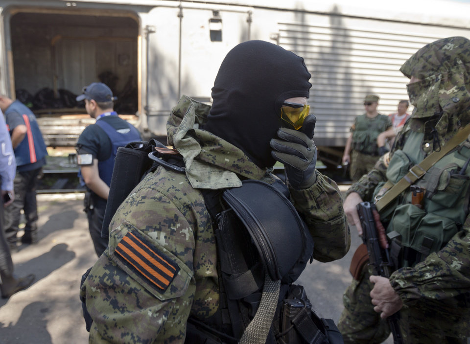 Photo - A pro-Russian rebel covers his nose due to the smell of decomposing bodies as members of the OSCE mission to Ukraine and Holland's National Forensic Investigations Team inspect a refrigerated train loaded with the bodies of passengers in Torez, eastern Ukraine, 15 kilometers (9 miles) from the crash site of Malaysia Airlines Flight 17, Monday, July 21, 2014. Another 21 bodies have been found in the sprawling fields of east Ukraine where Malaysia Airlines Flight 17 was downed last week, killing all 298 people aboard. International indignation over the incident has grown as investigators still only have limited access to the crash site and it remains unclear when and where the victims' bodies will be transported. (AP Photo/Vadim Ghirda)