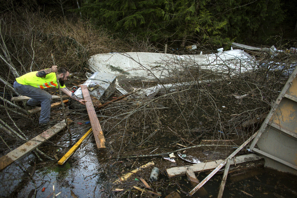Photo - Iraq War veteran and local Little League coach Matt Pater, 32, creates a bridge to check a floating section of a home in a field of debris following Saturday's destructive mudslide, near Oso Wash, Monday, March 24, 2014. The search for survivors of Saturday's deadly mudslide grew Monday to include scores of people who were still unaccounted for as the death toll from the wall of trees, rocks and debris that swept through the rural community rose to at least 14. (AP Photo/seattlepi.com, Joshua Trujillo)