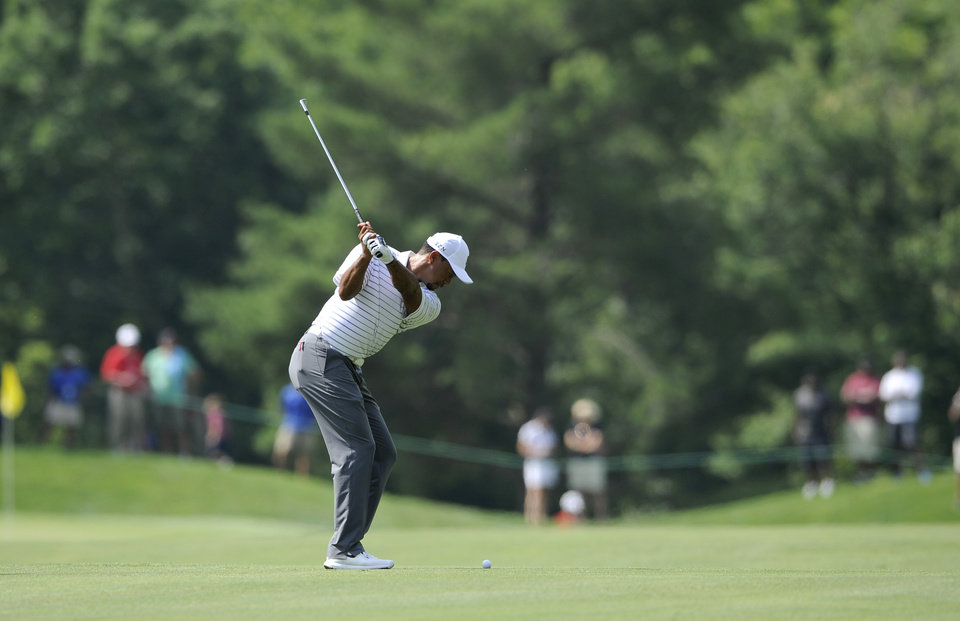 Photo - Tiger Woods hits on the fifth fairway during the Pro-Am at the Quicken Loans National golf tournament, Wednesday, June 25, 2014, in Bethesda, Md. (AP Photo/Nick Wass)