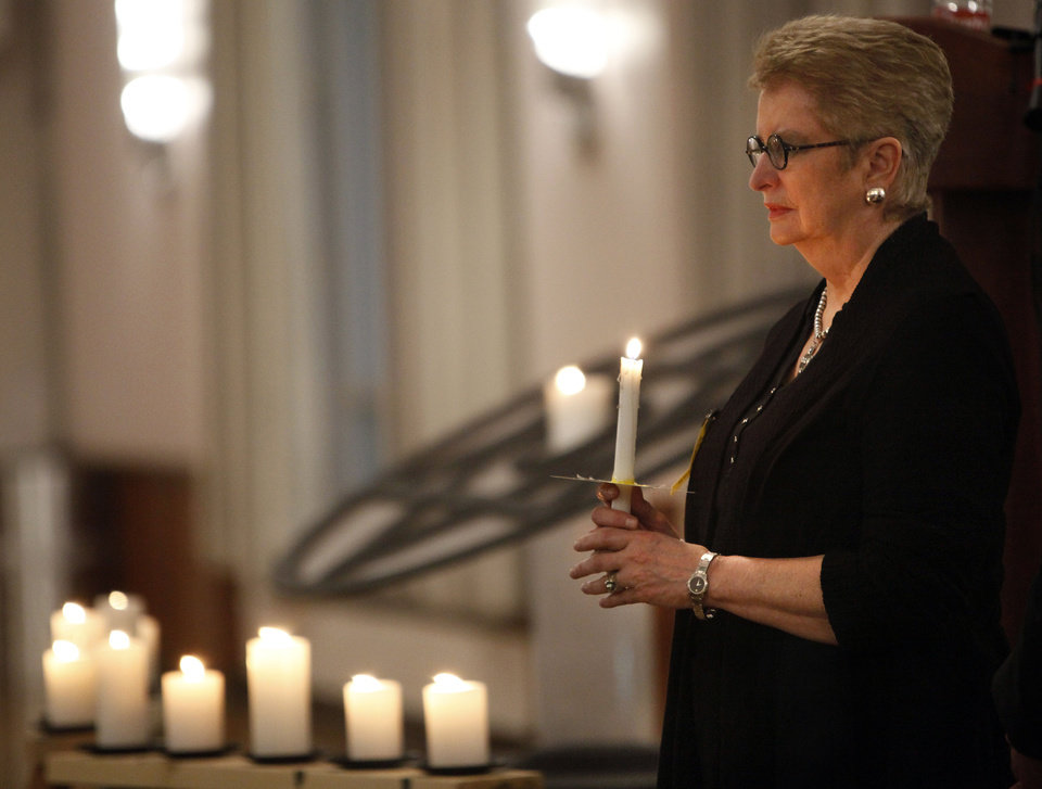 Photo - Yvonne Kauger lights a candle at the 2012 Holocaust Commemoration service Tuesday at the Civic Center Music Hall in Oklahoma City.  SARAH PHIPPS - SARAH PHIPPS