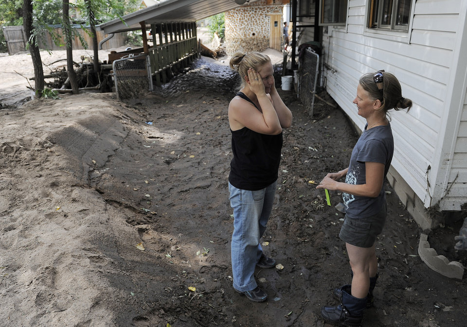 Photo - Neighbor Roslynn Regnery, left, talks with Emma Birath, right, as they check on their homes in Lyons, Colo., on Thursday, Sept. 19, 2013. The recovery process has begun  as people clean out flooded homes and businesses.   (AP Photo/Chris Schneider)