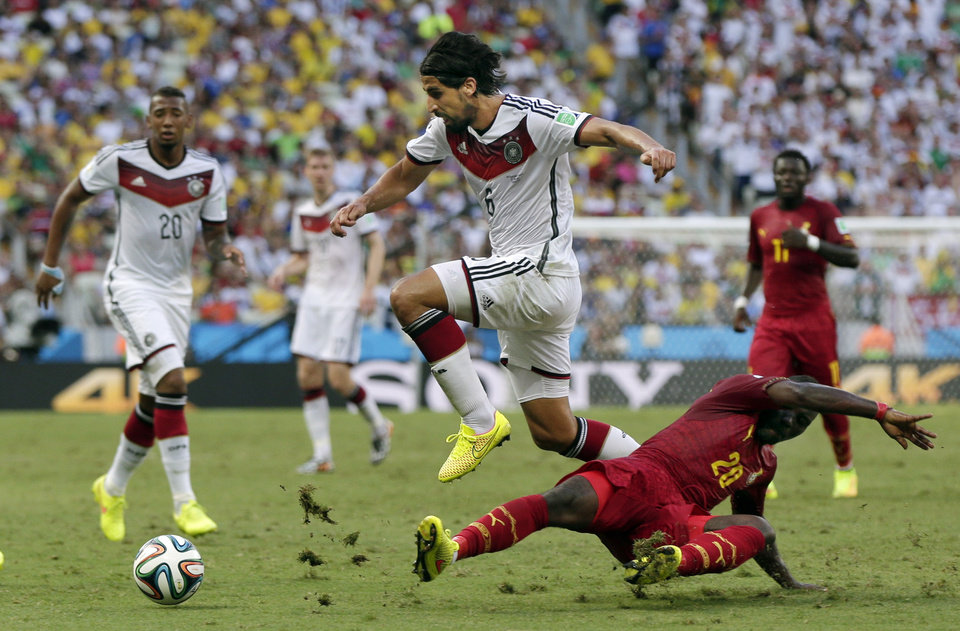 Photo - Germany's Sami Khedira, center, jumps over Ghana's Kwadwo Asamoah, right, to attack with the ball during the group G World Cup soccer match between Germany and Ghana at the Arena Castelao in Fortaleza, Brazil, Saturday, June 21, 2014. (AP Photo/Marcio Jose Sanchez)