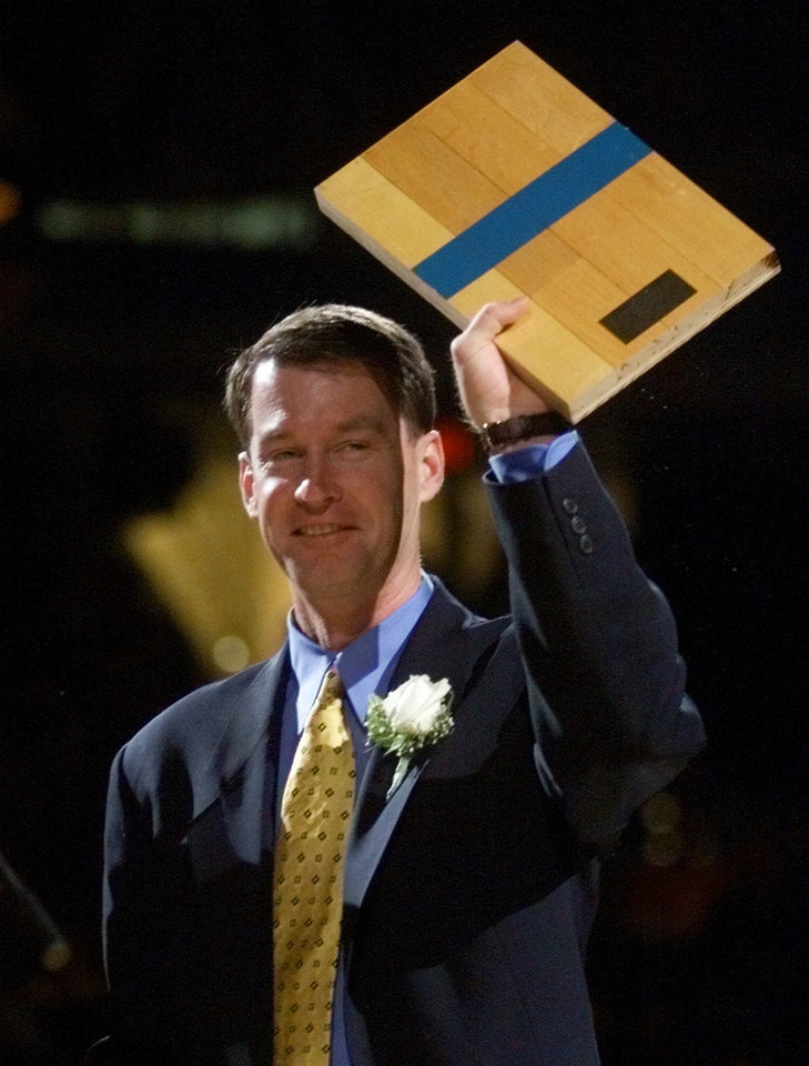 Photo - Former Cleveland Cavaliers guard Mark Price holds up a piece of the Richfield Coliseum floor Saturday, Nov. 13, 1999 at the Gund Arena in Cleveland. Price's jersey was retired Saturday in Cleveland.  (AP Photo/Tony Dejak)