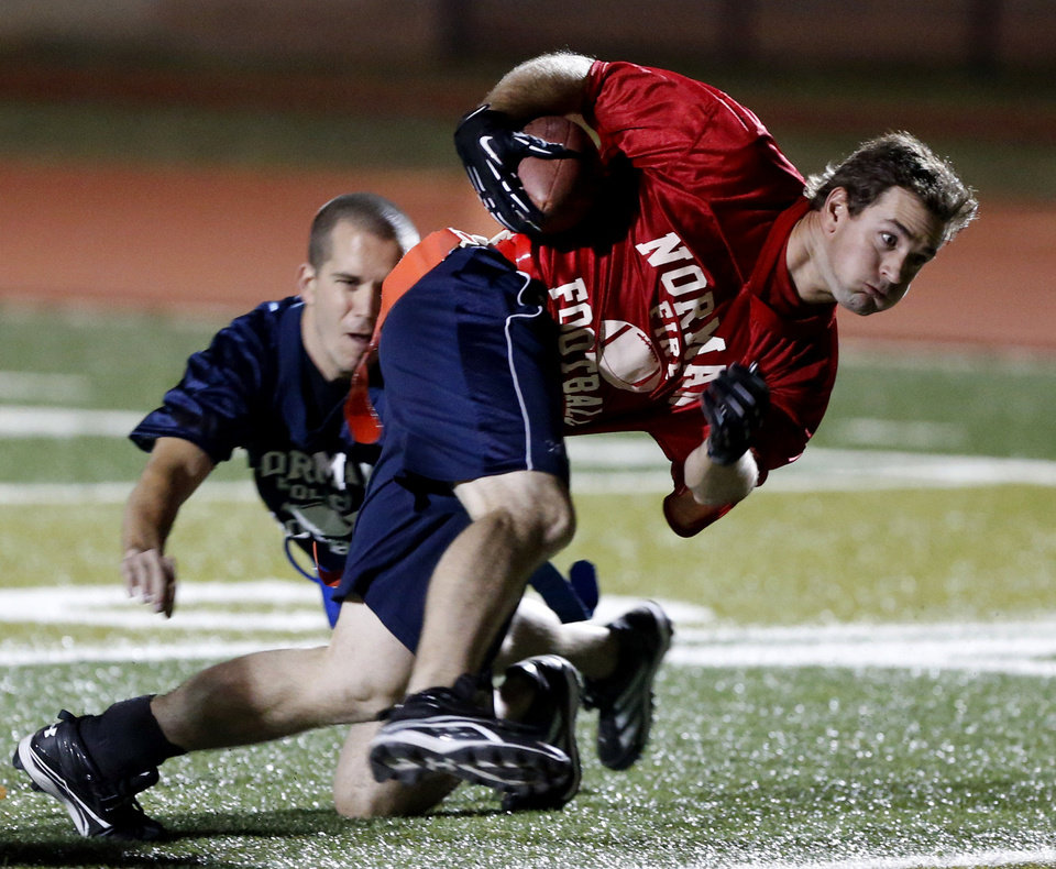 Above: Norman firefighter Justin Vinyard evades a tackle Tuesday in the Guns and Hoses charity football game.