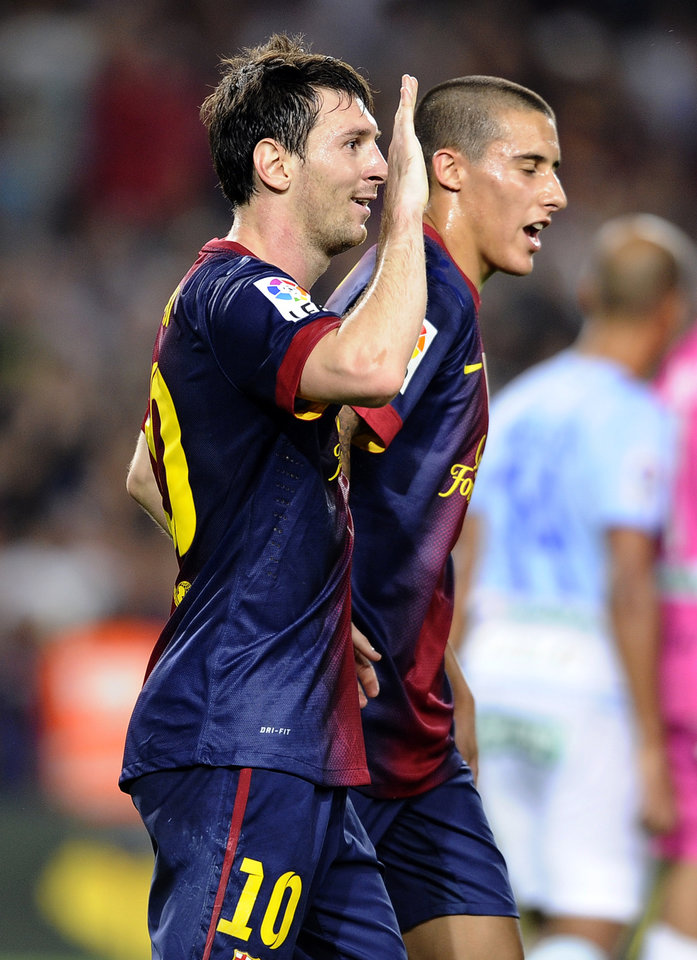 Photo -   FC Barcelona's Lionel Messi from Argentina, left, celebrates a goal against Granada during a Spanish La Liga soccer match at the Camp Nou stadium in Barcelona, Spain, Saturday, Sept. 22, 2012. (AP Photo/Manu Fernandez)