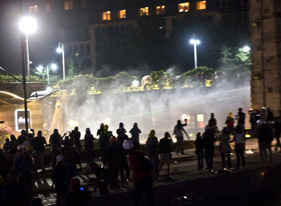 Photo - Water cannons are fired against protesters at the entrance of the Divan Hotel in Istanbul, Turkey, Saturday, June 15, 2013 after protesters were chased out of Gezi park. Protesters set up barricades and plumes of tear gas rose in Istanbul's streets into the early hours Sunday after Turkish riot police firing tear gas and water cannons cleared out the occupation of a park at the center of the strongest challenge to Prime Minister Recep Tayyip Erdogan's 10-year tenure. (AP Photo/Vadim Ghirda)
