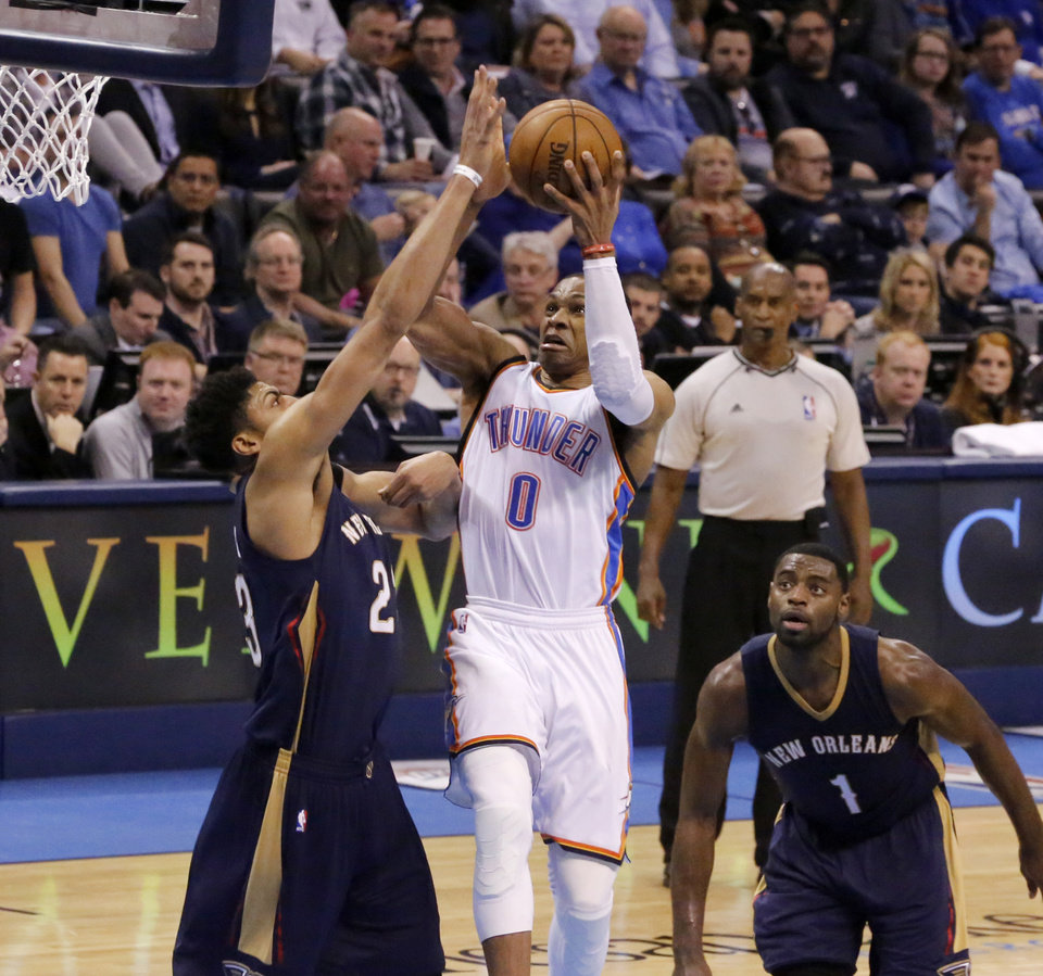 Photo - Oklahoma City's Russell Westbrook (0) goes to the basket between New Orleans' Anthony Davis (23) and Tyreke Evans (1) during an NBA game between the Oklahoma City Thunder and the New Orleans Pelicans at Chesapeake Energy Arena on Friday, Feb. 6, 2015. Photo by Bryan Terry, The Oklahoman