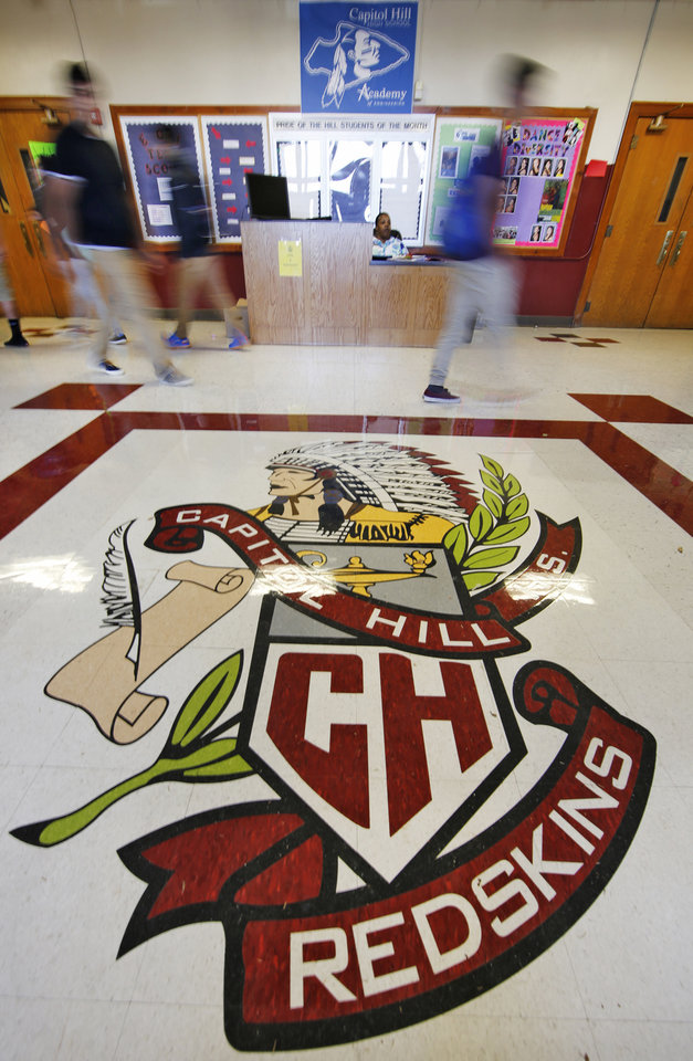 Photo -  Students walk past a Capitol Hill High School logo Tuesday at the school in Oklahoma City. The Oklahoma City School Board voted Monday night to ban Redskins as the school's nickname. Photo By Steve Gooch, The Oklahoman   Steve Gooch -