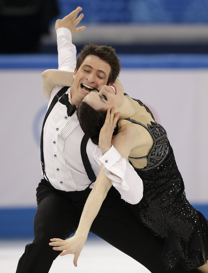 Photo - Tessa Virtue and Scott Moir of Canada compete in the ice dance short dance figure skating competition at the Iceberg Skating Palace during the 2014 Winter Olympics, Sunday, Feb. 16, 2014, in Sochi, Russia. (AP Photo/Darron Cummings)