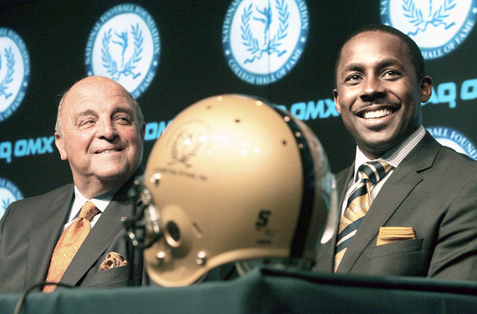 Photo - Barry Alvarez, left, former Wisconsin coach, and Desmond Howard, former Michigan receiver, smile during a news conference Thursday announcing the 2010 College Football Hall of Fame Class. AP photo