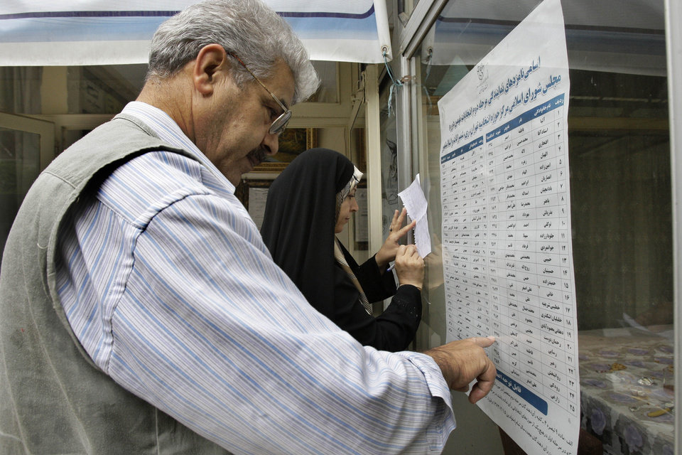 Photo -   An Iranian couple checks the list of the candidates in the parliamentary runoff elections at a polling station in Tehran, Iran, Friday, May 4, 2012. The country has begun runoff elections for more than one-fifth of parliamentary seats. Friday's report says 130 hopefuls will compete for 65 seats in 33 constituencies including the capital Tehran with 25 undecided seats. (AP Photo/Vahid Salemi)