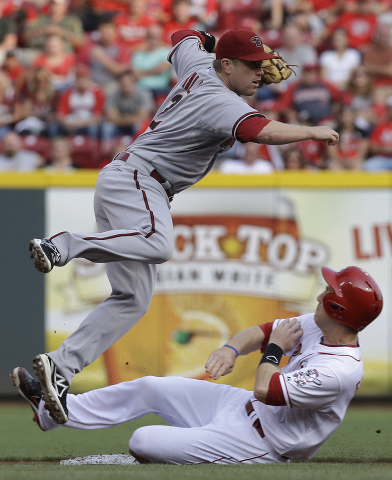 Photo - Cincinnati Reds' Todd Frazier slides hard into second base after he was forced out by Arizona Diamondbacks second baseman Aaron Hill (2) in the first inning of a baseball game, Tuesday, July 29, 2014, in Cincinnati. Hill threw to first to complete the double play. (AP Photo/Al Behrman)