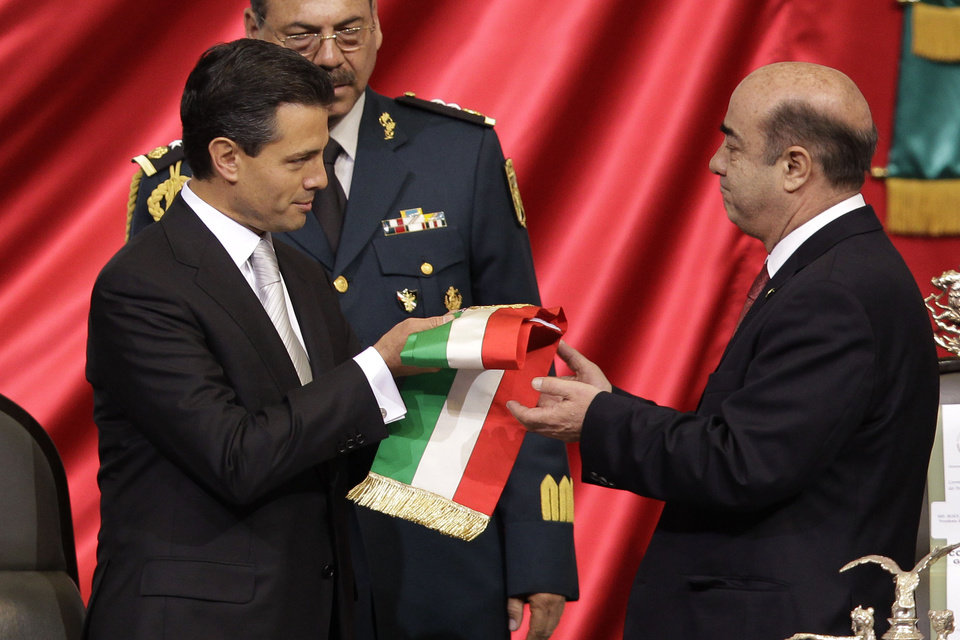 Photo - Enrique Pena Nieto, left, receives the presidential sash from Jesus Murillo Karam, president of the lower house, during the presidential inauguration ceremony at the National Congress in Mexico City, Saturday, Dec. 1, 2012. Pena Nieto took the oath of office as Mexico's new president on Saturday, bringing the old ruling party back to power after a 12-year hiatus amid protests inside and outside the congressional chamber where he swore to protect the constitution and laws of the land. AP Photo/Alexandre Meneghini)