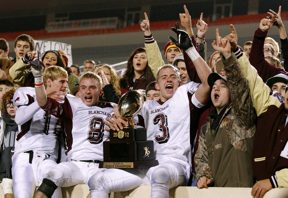 Blanchard's Brock Lamle, left, Trevor Harrison, and Zach Hill, at right, celebrate with the crowd after winning  the Class 3A football championship between Blanchard and Kingfisher at Boone Pickens Stadium in Stillwater, Okla., Friday, Dec. 7, 2012. Blanchard won 28-21. Photo by Bryan Terry, The Oklahoman