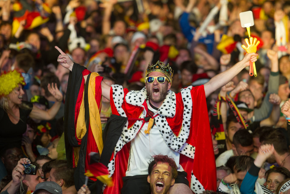 Photo - German soccer fans react after the deciding goal  for Germany in the final of  the Brazil World Cup 2014 between Germany and Argentina played  in Rio de Janeiro, Brazil, at a public viewing  area  called 'Fan Mile' in Berlin, Sunday, July 13, 2014.  Germany won by 1-0.  (AP Photo/Steffi Loos)