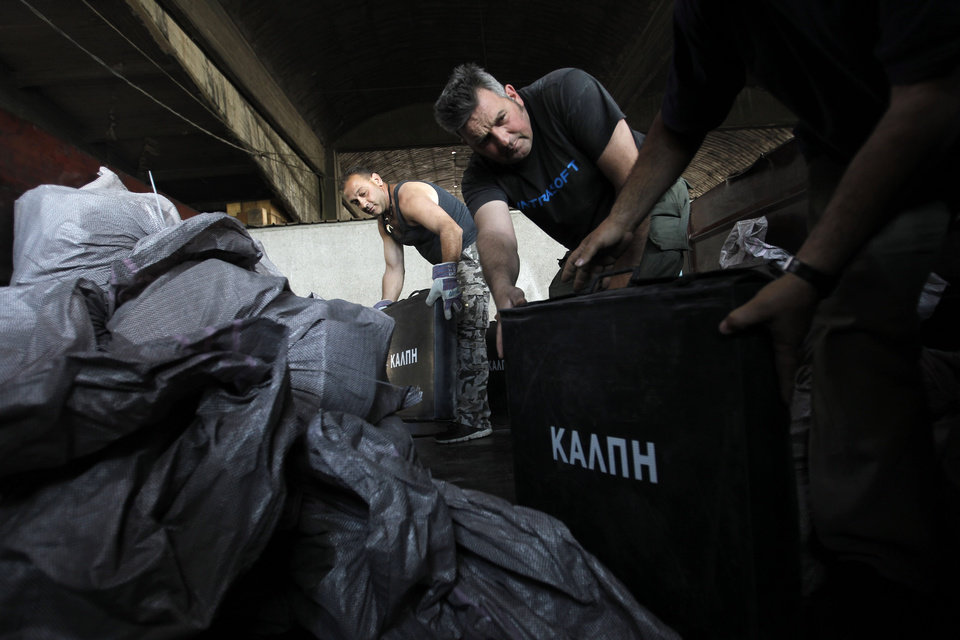 Photo -   Worker fill a truck with voting papers and ballot boxes in Athens' municipality's warehouse, before delivering them to the polling stations around Athens , on Thursday, May 3, 2012. Greeks head to the polls in early general elections on May 6 .(AP Photo/Petros Giannakouris)