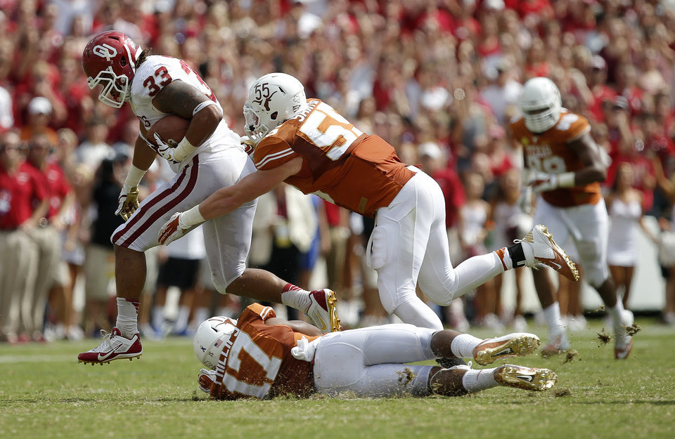 Photo - OU's Trey Millard (33) leaps past UT's Adrian Phillips (17) and Dalton Santos (55) during the Red River Rivalry college football game between the University of Oklahoma Sooners and the University of Texas Longhorns at the Cotton Bowl Stadium in Dallas, Saturday, Oct. 12, 2013. Texas won 36-20. Photo by Bryan Terry, The Oklahoman