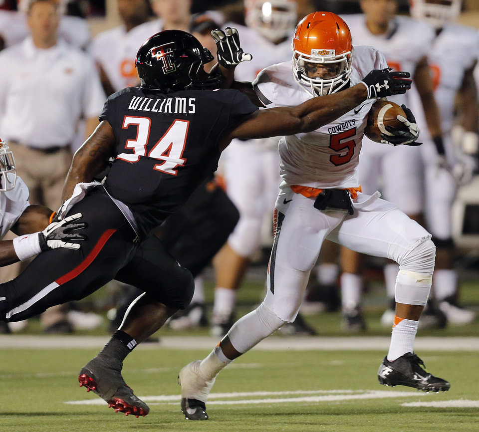 Oklahoma State 's Josh Stewart (5) runs past Texas Tech's Kenny Williams (34) during the college football game between the Oklahoma State University Cowboys (OSU) and the Texas Tech University Red Raiders (TTU) at Jones AT&T Stadium in Lubbock, Tex. on Saturday, Nov. 2, 2013.  Photo by Chris Landsberger, The Oklahoman