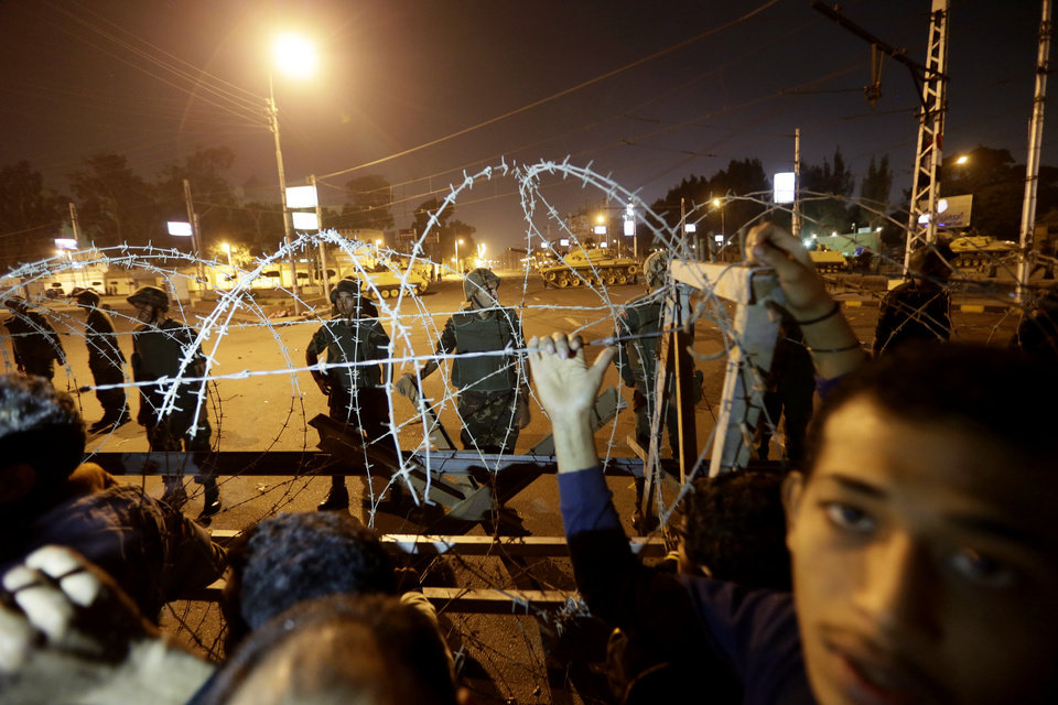 Photo - Egyptian protesters stand behind barbed wire on a road leading to the presidential palace during a protest against Egyptian President Mohammed Morsi, in Cairo, Egypt, Thursday, Dec. 6, 2012. The Egyptian army has deployed tanks outside the presidential palace in Cairo following clashes between supporters and opponents of Mohammed Morsi that left several people dead and hundreds wounded. (AP Photo/Hassan Ammar)