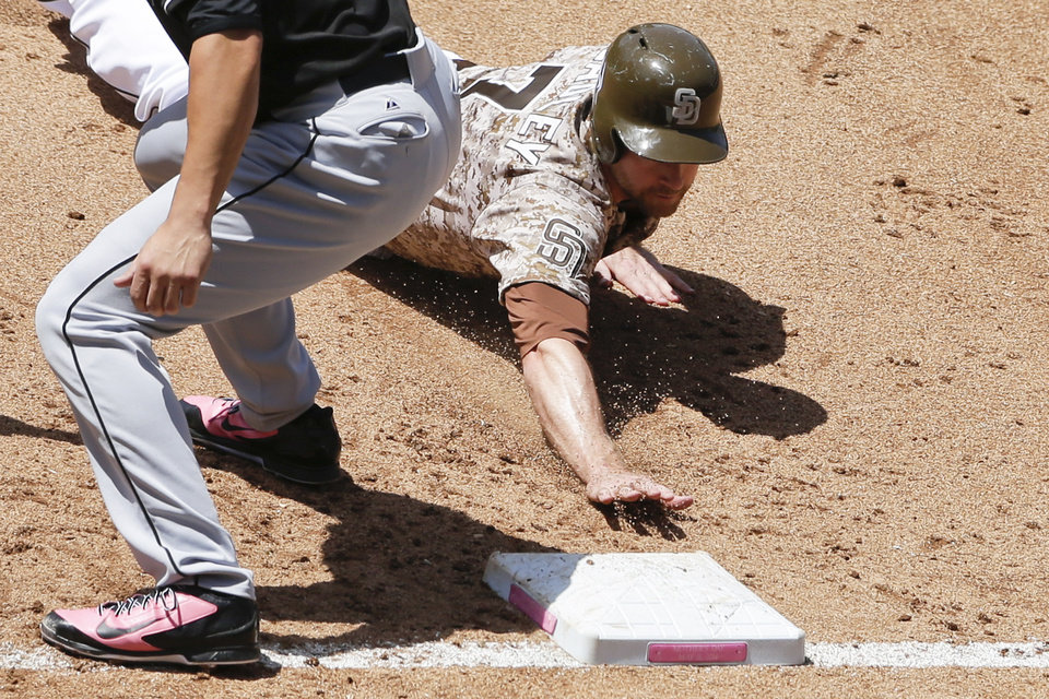 Photo - San Diego Padres' Chase Headley gets back safely to first while playing the Miami Marlins during the fourth inning of a baseball game Sunday, May 11, 2014, in San Diego. (AP Photo/Gregory Bull)