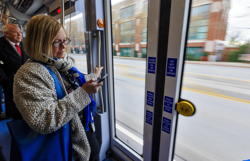 Photo - Jill Adler uses her phone as she rides on the new streetcar during the grand opening celebration day of the Oklahoma City streetcar system in downtown Oklahoma City, Okla. on Friday, Dec. 14, 2018. Photo by Chris Landsberger, The Oklahoman