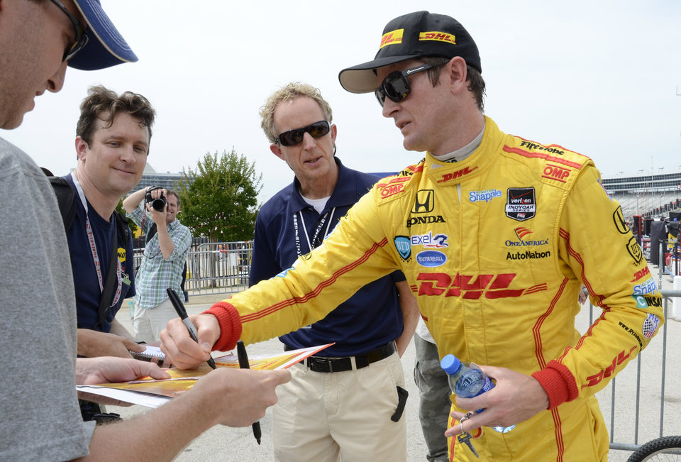 Photo - Ryan Hunter-Reay signs an autograph after the IndyCar auto racing practice session at Texas Motor Speedway in Fort Worth, Friday, June 6, 2014. (AP Photo/Larry Papke)